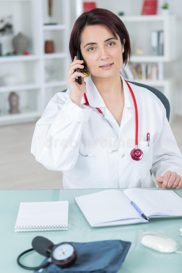 Female doctor talking on phone in office. Female doctor talking on phone in her office royalty free stock photo