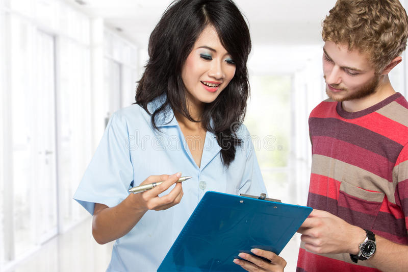Female doctor talking to her male patient stock photo