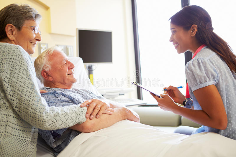 Female Doctor Talking To Senior Couple In Hospital Room. Holding Clipboard And Pen Taking Notes royalty free stock photography