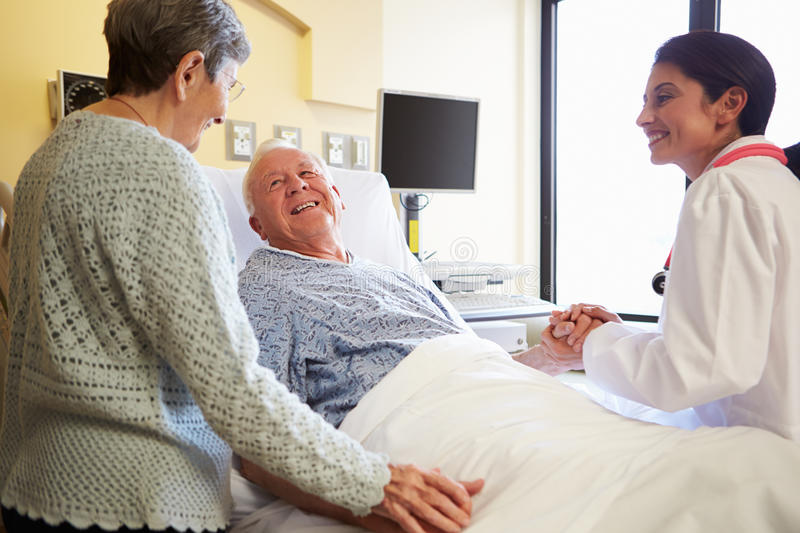 Female Doctor Talking To Senior Couple In Hospital Room. Holding Patient Hand Smiling royalty free stock photo