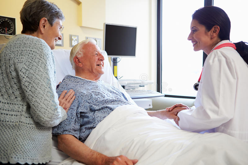 Female Doctor Talking To Senior Couple In Hospital Room. Looking At Patient Smiling royalty free stock photography