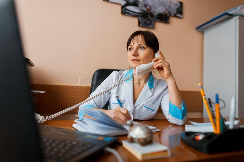 A female doctor talks on the phone with one of the patients and takes notes on a notepad. The doctor works. royalty free stock photo
