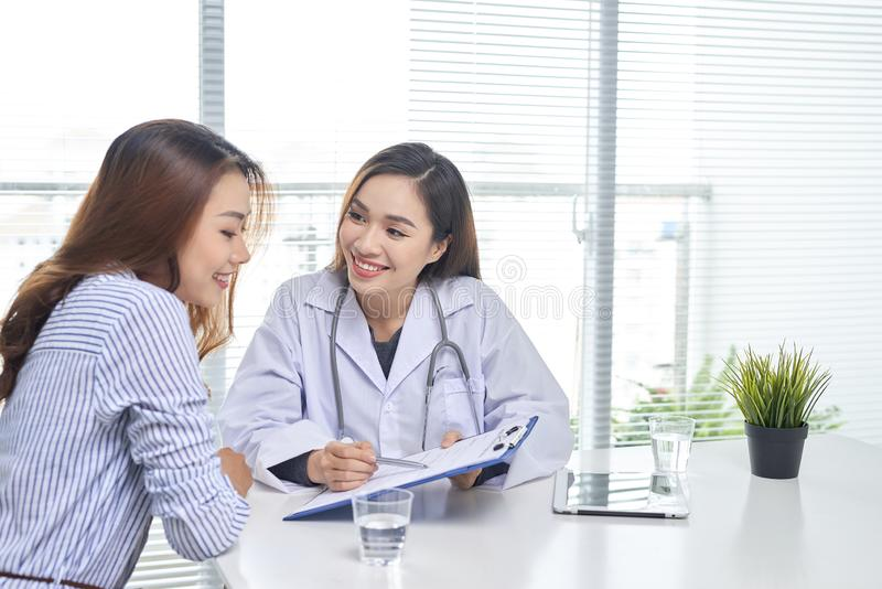 Female doctor talks to female patient in hospital office while writing on the patients health record on the table. Healthcare and stock image