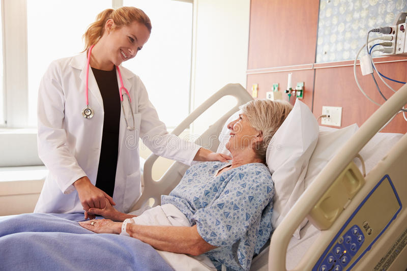 Female Doctor Talks To Senior Female Patient In Hospital Bed stock photography