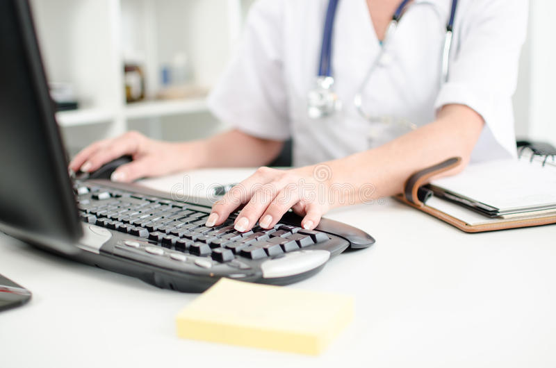 Female doctor taping on a computer keyboard royalty free stock photos