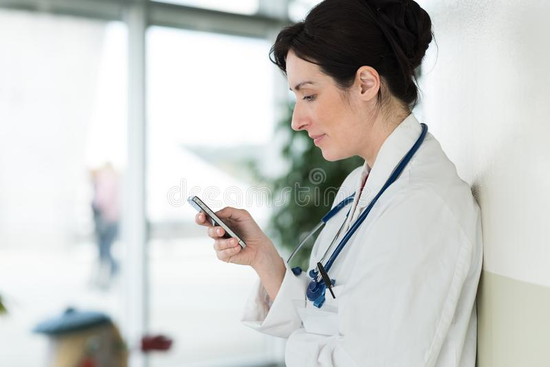 Female doctor texting on smartphone in medical office royalty free stock image