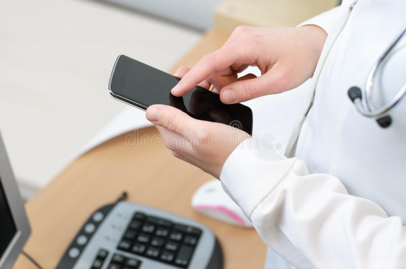 A female doctor texting on smartphone. In medical office royalty free stock photography