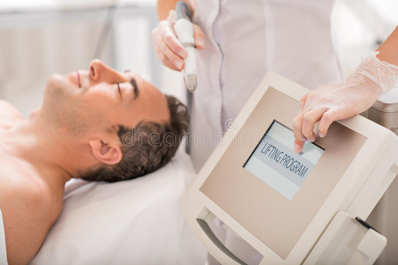 Female doctor undergoing electrotherapy at wellness center royalty free stock image