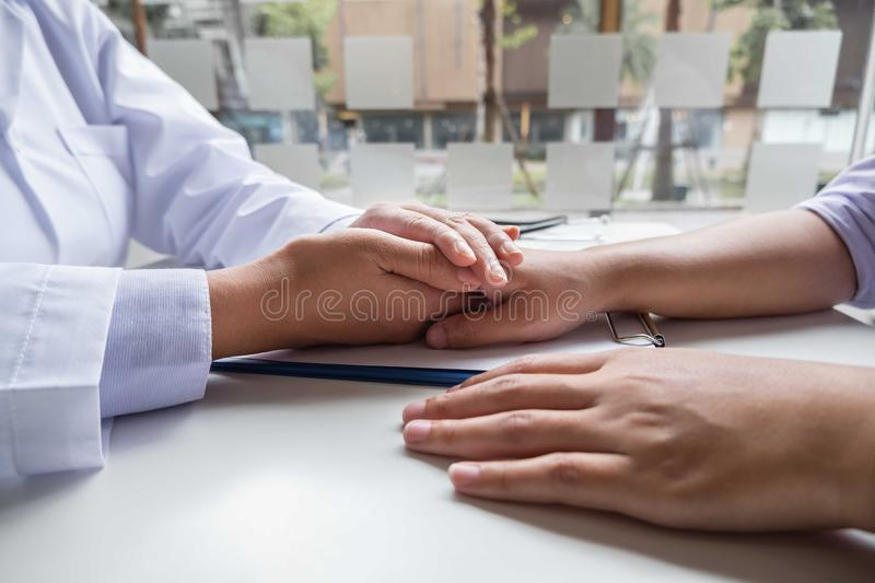 The female doctor uses a friendly hand to hold the patient`s hand to give confidence and show care about health care. Medical stock image
