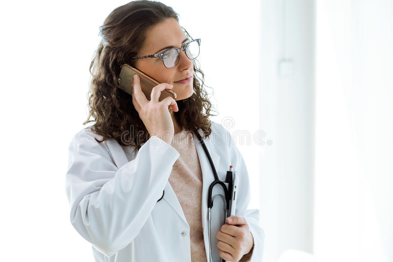 Female doctor using her mobile phone in the consultation. Portrait of female doctor using her mobile phone in the consultation stock photos