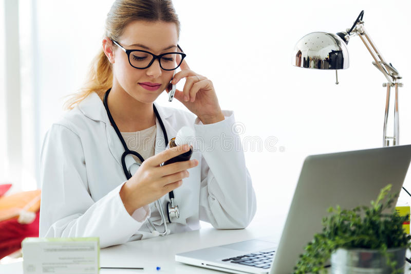 Female doctor using his mobile phone in the office. Portrait of female doctor using his mobile phone in the office stock image