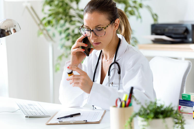 Female doctor using his mobile phone in the office. Portrait of female doctor using his mobile phone in the office royalty free stock photography
