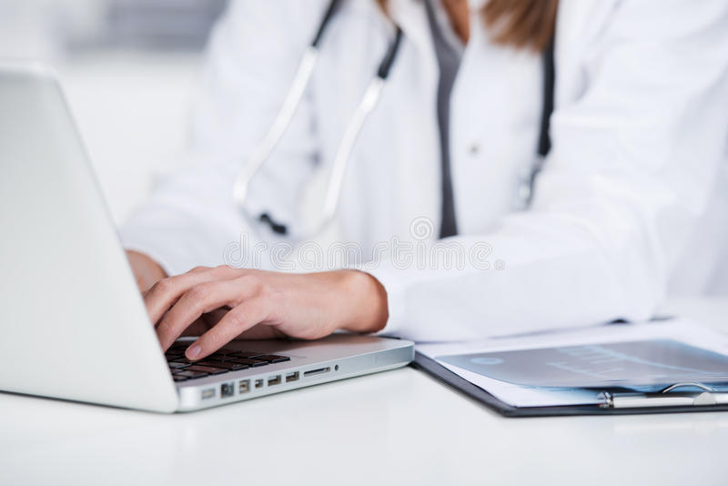 Female Doctor Using Laptop At Desk royalty free stock images
