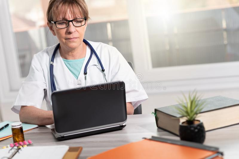 Female doctor using laptop stock photography
