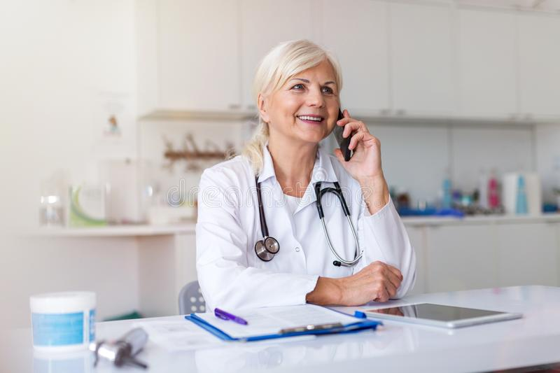 Female doctor using mobile phone in her office. Confident female doctor using mobile phone in her office stock images