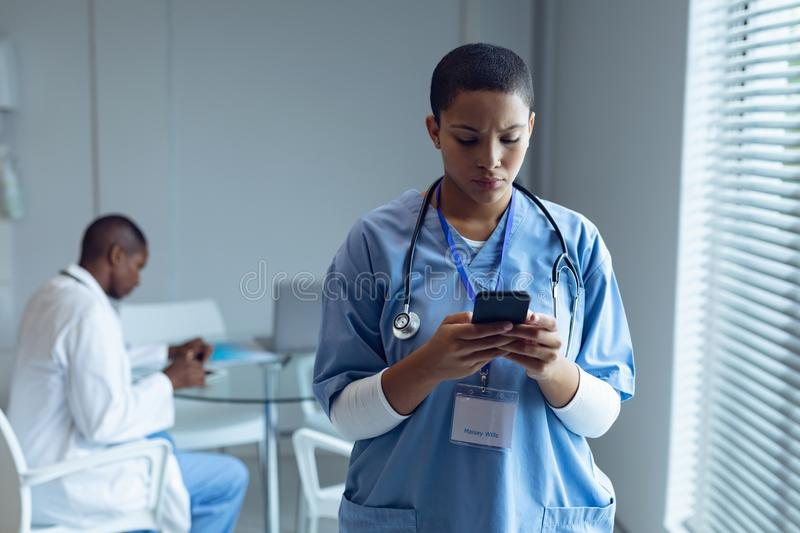 Female doctor using mobile phone in hospital. Front view of young mixed race female doctor using mobile phone while African american doctor working on desk in stock photo