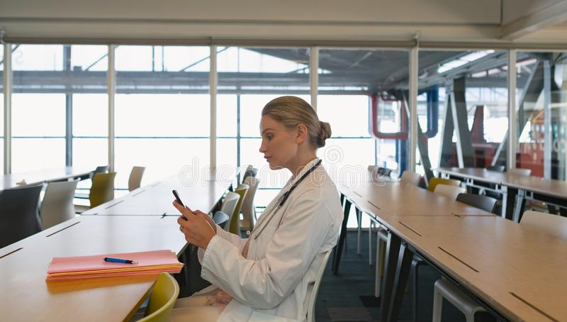 Female doctor using mobile phone in the medical seminar. Side view of beautiful Caucasian female doctor using mobile phone in the medical seminar stock photos