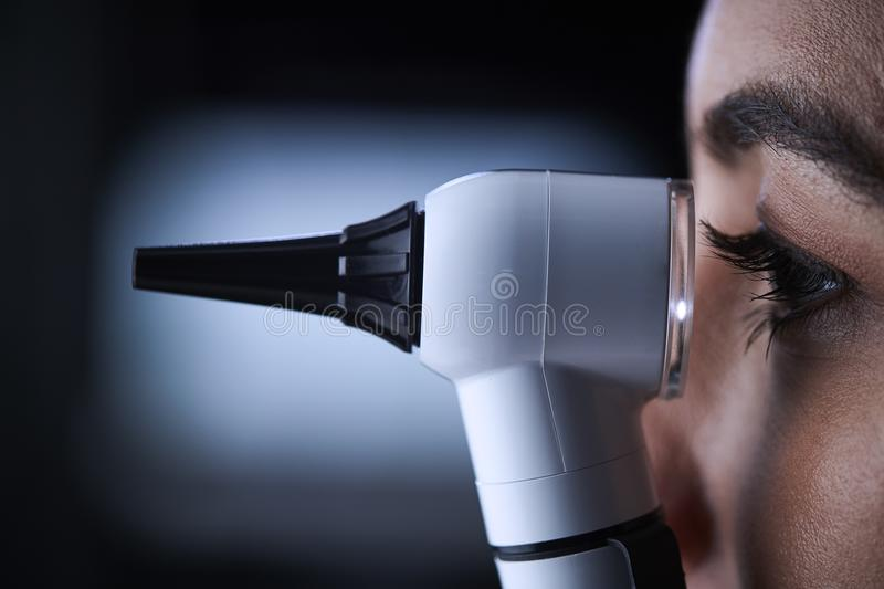 Female doctor using otoscope, side view, close up royalty free stock images