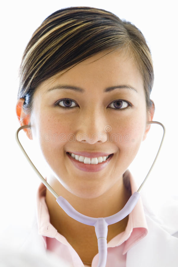 Female doctor using stethoscope, smiling, portrait, close-up, cut out stock photo