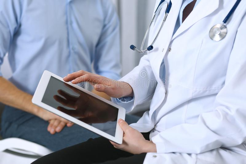 Female doctor using touchpad or tablet computer while consulting man patient in hospital. Medicine and healthcare stock images