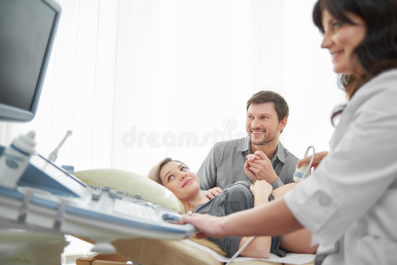Female doctor using ultrasound diagnosing pregnant woman. stock images