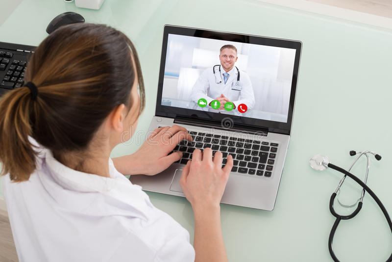 Female Doctor Video Chatting On Laptop stock image