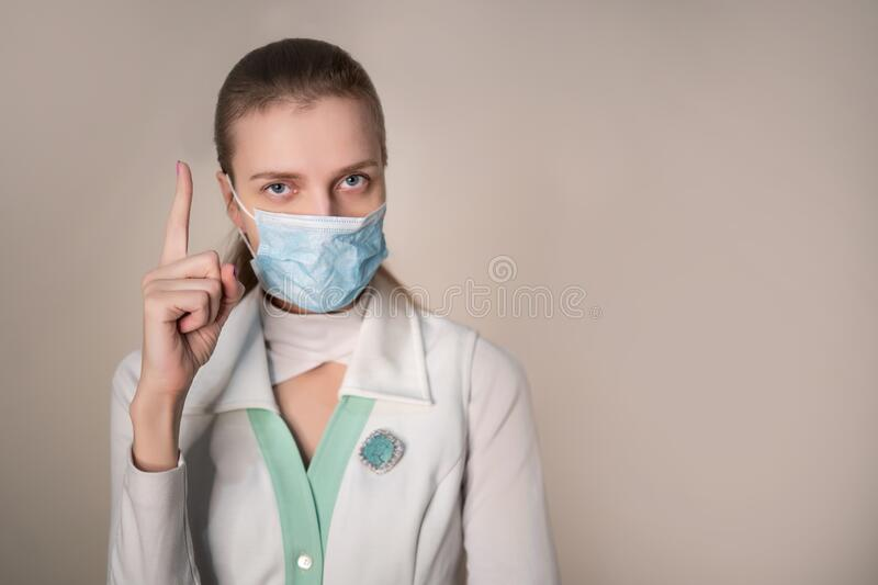 Female doctor wearing protective blue mask royalty free stock image