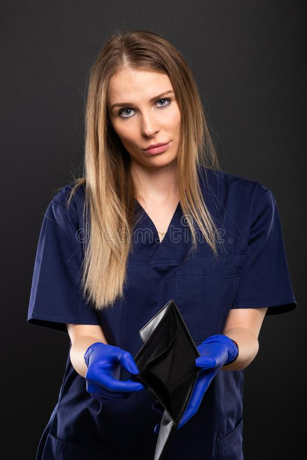 Female doctor wearing scrubs and gloves showing empty wallet stock photo
