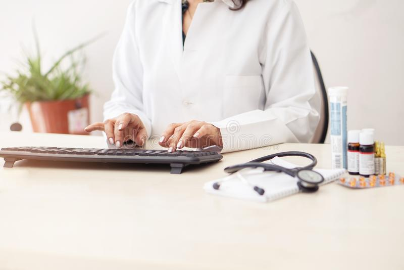 Female doctor in white lab coat,hands typing on laptop computer keyboard with medical stethoscope and  medicine on the mirror desk stock images