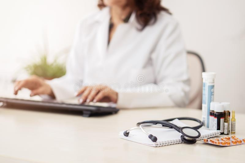 Female doctor in white lab coat,hands typing on laptop computer keyboard with medical stethoscope and  medicine on the mirror desk royalty free stock photos