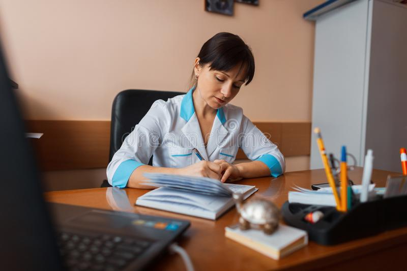 A female doctor in white medical uniform is sitting at a wooden table in the office and makes up a work schedule for the staff stock photos