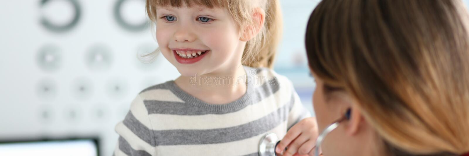 Female doctor working with cute smiling little girl at her office royalty free stock photography