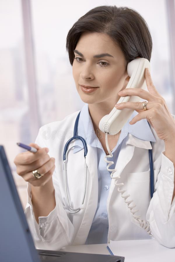 Female doctor working at desk royalty free stock image