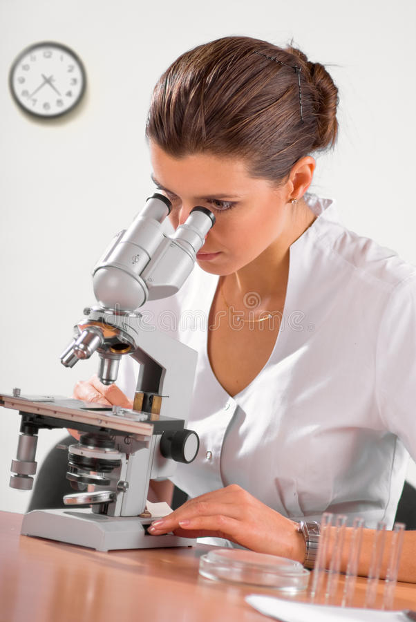 Female doctor working with a microscope. Young female doctor working with a microscope in a laboratory royalty free stock image