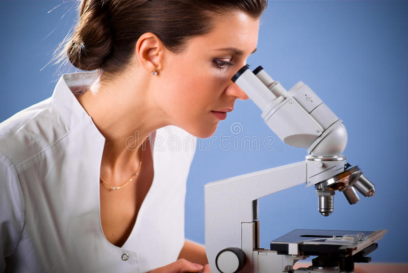 Female doctor working with a microscope. Young female doctor working with a microscope in a laboratory; blue background stock image