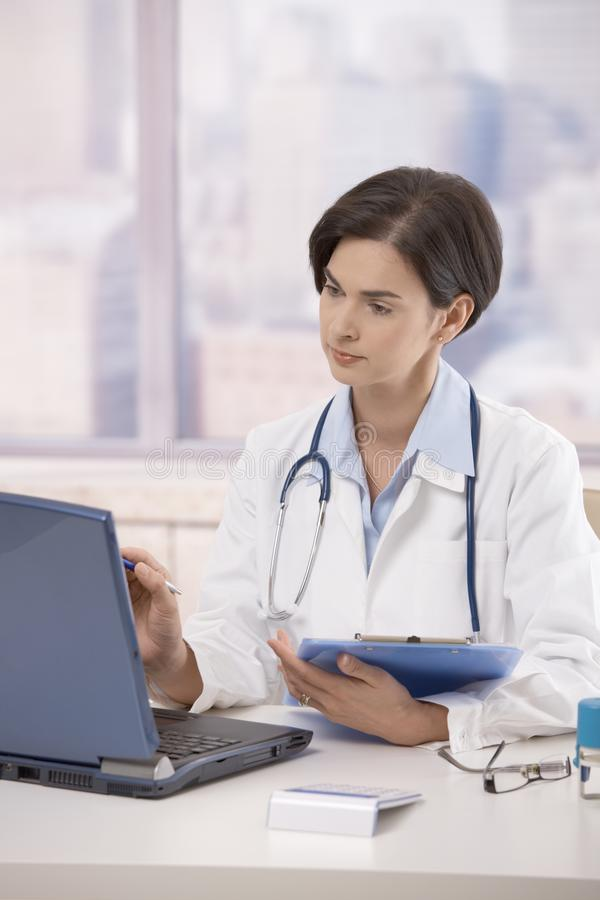 Female doctor working in office stock photo