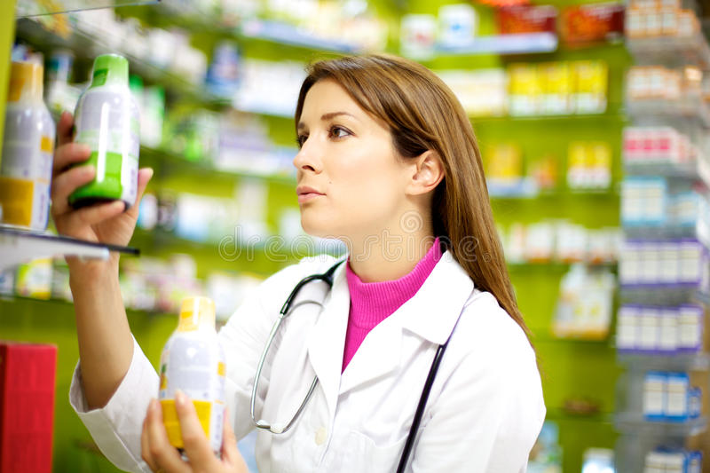 Female doctor working in pharmachy. Young good looking doctor putting order in her pharmacy with medicine stock photo
