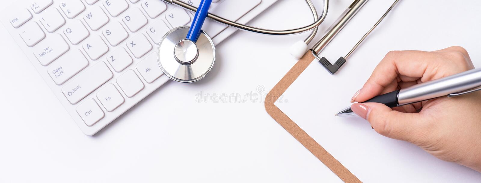 Female doctor writing a medical record case over clipboard on white working table with stethoscope, computer keyboard. Top view, royalty free stock photo