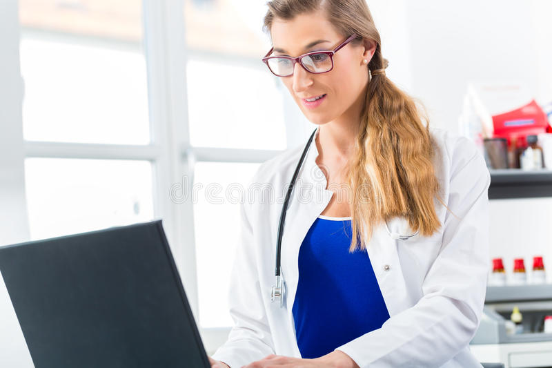Download Female Doctor Writing On Pc In Her Clinic Stock Photo - Image: 32187884