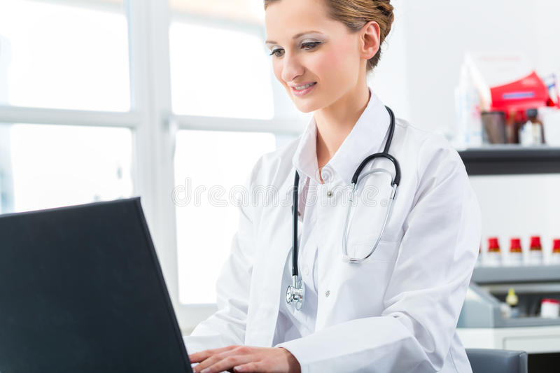 Download Female Doctor Writing On Pc In Her Clinic Stock Photo - Image: 32787780