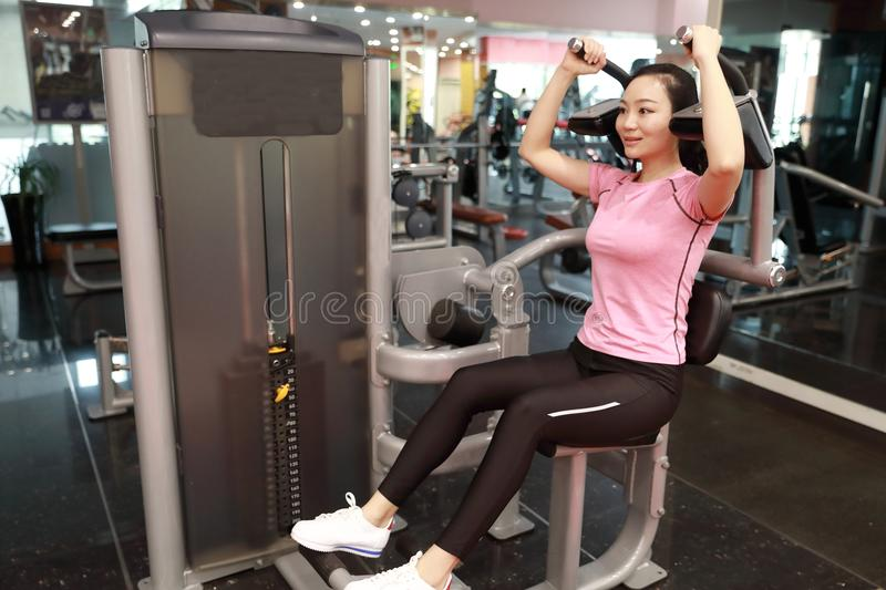 In fitness center woman working. Slim girl sitting and hard working on sport equipment , Female doing push ups in gym stock images