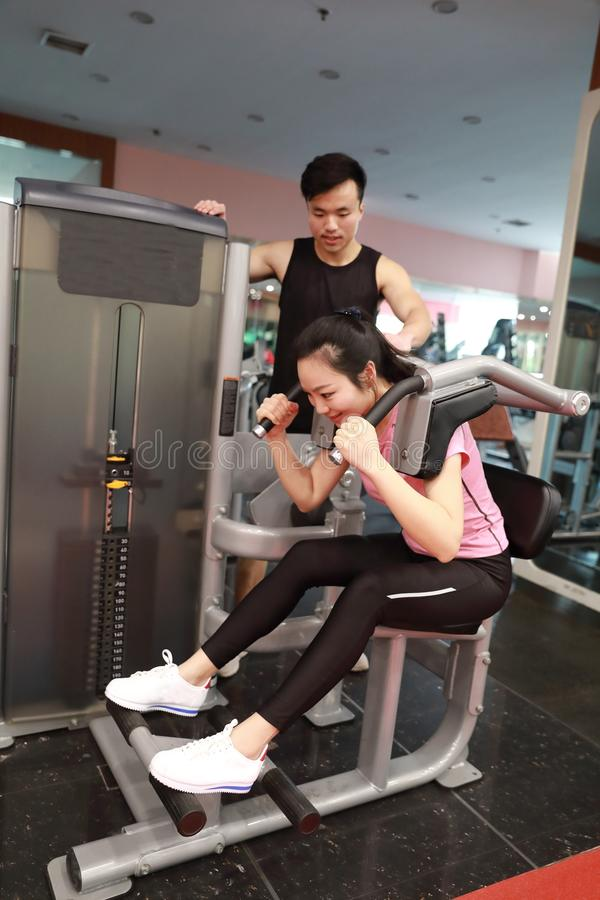 In fitness center woman working. Slim girl sitting and hard working on sport equipment , Female doing push ups in gym. Female doing push ups exercise in gym With stock images