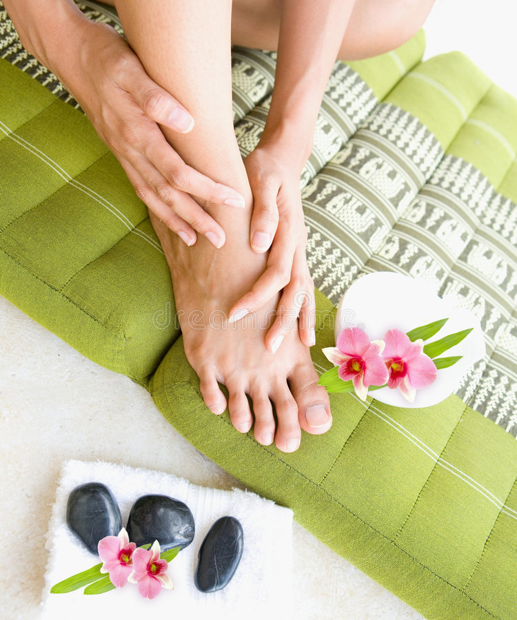 Female doing self foot massage. With aromatherapy oil royalty free stock photography