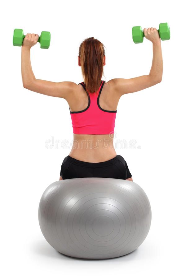 Female doing shoulder press. Photo of a female from behind doing dumbbell shoulder press while sitting on an exercise ball stock image