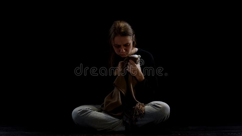 Female domestic violence victim hugging teddy bear, happy childhood memories. Stock photo royalty free stock photo