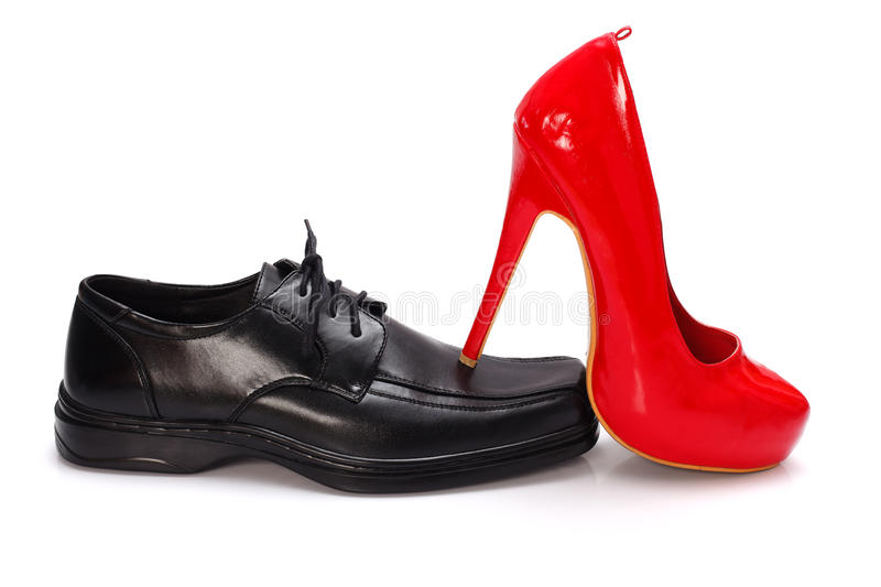 Female dominance. High-heeled red woman shoe on black man shoe - dominance concept stock photography