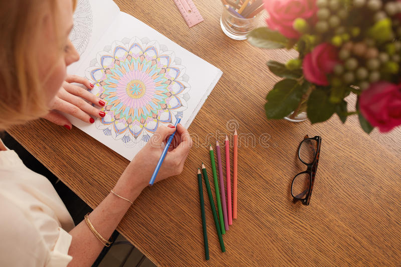 Female drawing in adult coloring book at home stock images