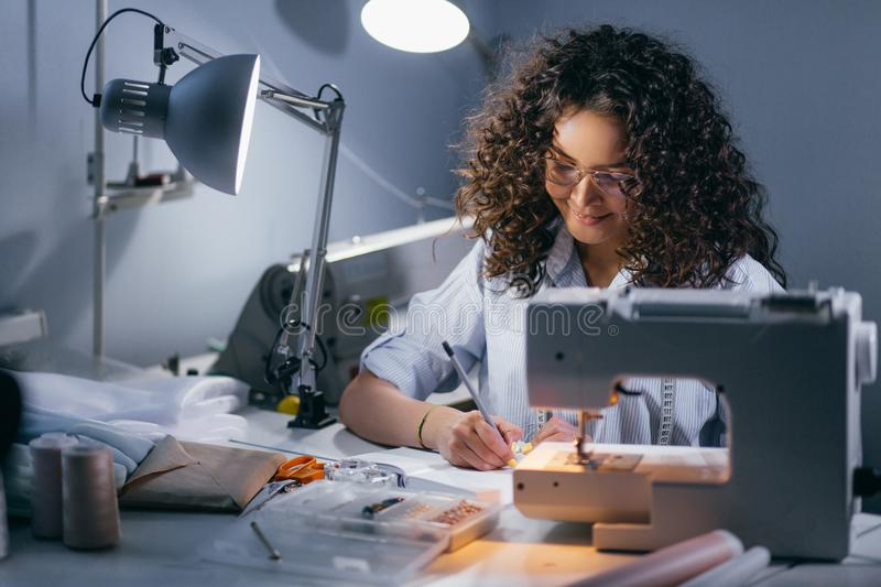 Female is drawing up a draft in front of sewing machine stock images