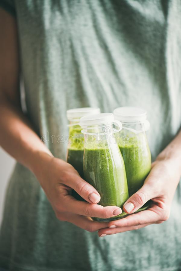 Female in dress holding bottles of green smoothie or juice. Winter seasonal smoothie drink detox. Female in dress holding bottles of green smoothie or juice in stock photo
