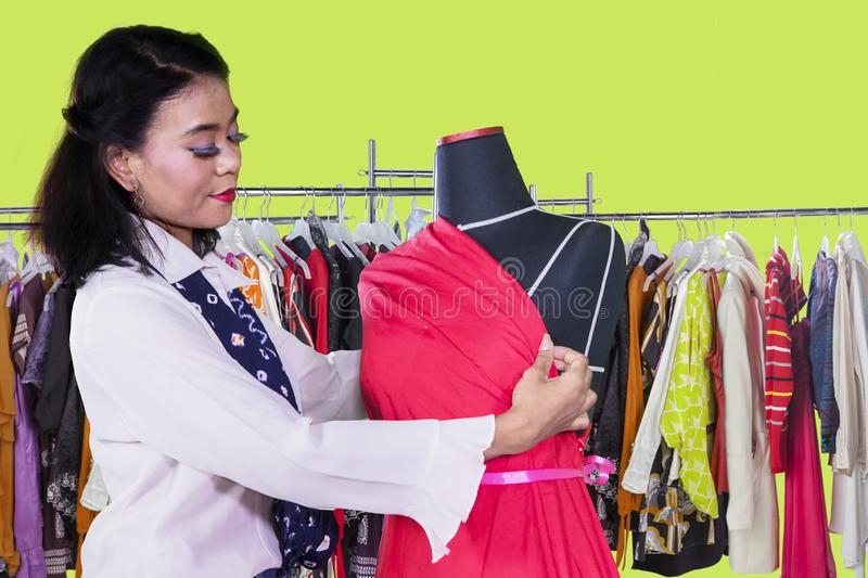 Female dressmaker adjusts red fabric on a mannequin royalty free stock image